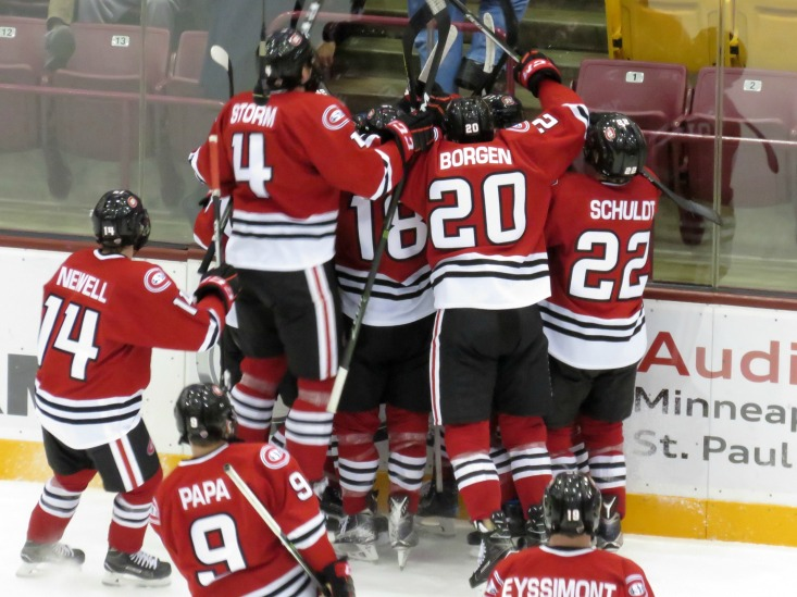 SCSU player mob the Huskies Jake Wahlin after he scores the overtime winner vs Minnesota Friday (photo prout)