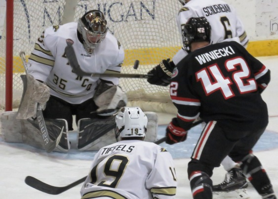 Blake Winiecki looks on as a puck deflects off of WMU goaltender Trevor Gorsuch (photo prout)